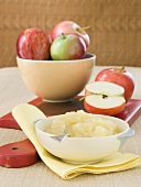 Bowl of Homemade Applesauce with a Bowlful Fresh Apples; Cutting Board