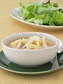 Bowl of Chicken Noodle Soup; Side Salad in Background