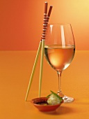 Glass of White Wine with Chopsticks and Asian Appetizer