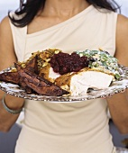 Woman holding plate of roast turkey with accompaniments