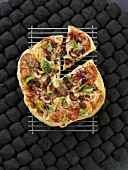 Grilled pizza with sausage, onion and basil