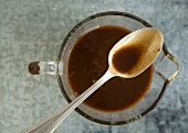 Spoon With Balsamic Vinaigrette Resting on Pitcher of Vinaigrette