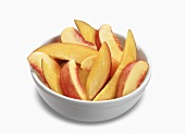 Bowl of Peach and Mango Slices on a White Background