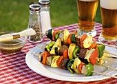 Grilled Kabobs Piled on a Plate; On an Outdoor Table; Beer