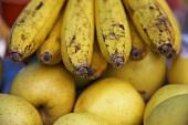 Ein Bund reife Bananen auf gelben Äpfeln liegend