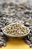 Bowl of Shelled Sunflower Seeds Surrounded by Whole Seeds