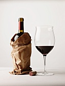 Bottle of Red Wine in a Brown Paper Bag; Glass of Red Wine