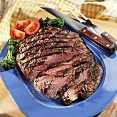 Grilled, Sliced Flank Steak on a Blue Platter