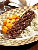 Grilled Steak Over Mashed Potatoes with Sliced Carrots
