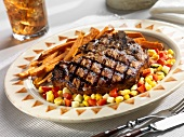 A Grilled Pork Chop with Corn Relish and Sweet Potato Fries