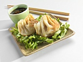 Two Potstickers with Soy Dipping Sauce and Chopsticks