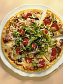 Pepperoni Pizza Sliced and Topped with Greens, From Above