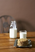 Stack of Chocolate Chip Cookies with Glass of Milk, Bottle of Milk on Table