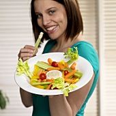 Woman Holding Vegetable Platter in One Hand and Celery in the Other