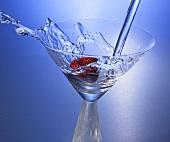 Martini in Glas mit Erdbeere eingiessen