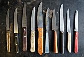 Many Assorted Steak Knives Lined Up