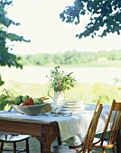 Outdoor Farm Table with a Bowl of Fresh Vegetables, Stacked Plates, Flowers