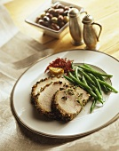 Slices of Herbed Pork Roast with Green Beans on a Plate, Salt and Pepper