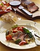 Sliced Steak with Vegetables on a Plate with Crusty Bread and Red Wine