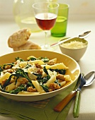 Bowl of Penne Pasta with Broccoli Rabe and Sausage Topped with Parmesan Cheese