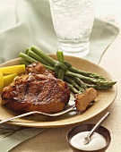 Grilled Pork Chop with Piece on a Fork, Asparagus, On a Plate