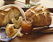 Rustic Loaves of Bread with Marmalade on Wooden Table