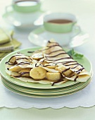 Banana Crepes with Chocolate Drizzles on a Stack of Green Plates