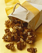 Caramel nut popcorn spilling from an overturned paper bag