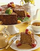 Slice of Spice Cake with Red and Golden Raspberries in Bourbon Sauce, Whole Cake with Slice Removed
