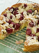 Raspberry Almond Cake with a Slice Removed on Cooling Rack