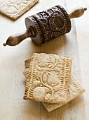 Mehrere Mürbteigplätzchen mit Ornament-Oberfläche und eine hölzerne Teigrolle