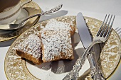 Three Beignets Topped with Powdered Sugar on a Plate; Tea