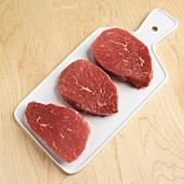Three raw beef steaks on a chopping board