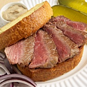 Sliced Rare Steak Sandwich on Texas Toast; Onions and Pickles