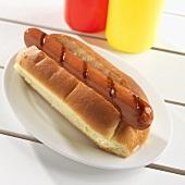 Ein gegrillter Hot Dog im Brötchen