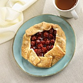 Rustic Cherry Pastry on a Blue Plate; Cup of Tea