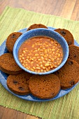 Slices of Boston Brown Bread with Raisins with a Bowl of Baked Beans
