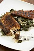Grilled Mahi Mahi Over Greens on a White Plate; Piece on Fork
