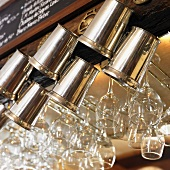 Metal Beer Mugs and Wine Glasses Hanging From a Bar