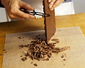 Chef Making Chocolate Curls From a Bar of Chocolate with a Peeler