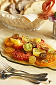 Heirloom Tomato Salad on a Glass Plate; Sliced Bread