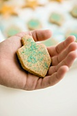 A hand holding a dreidel-shaped biscuit decorated with blue sprinkles