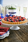 Whole Fruit Tart on a Pedestal Dish on a Wooden Table