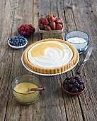 Tart Surrounded by Assorted Berries for Topping; On Wood