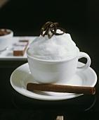 Tasse Kakao mit Milchschaum und Hippenröllchen