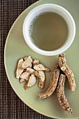 Ginsengwurzelstücke und eine Tasse Ginseng Tea