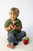 Little Boy Sitting, Holding Half an Apple, Two Whole Apples