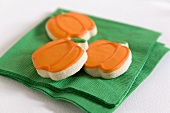 Three pumpkin biscuits for Halloween on a green napkin