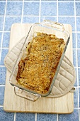 Apple Crisp in Baking Dish on a Pot Holder on Cutting Board, From Above