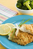 Fried White Fish Fillets on a Plate with Lemon Slices and Chives